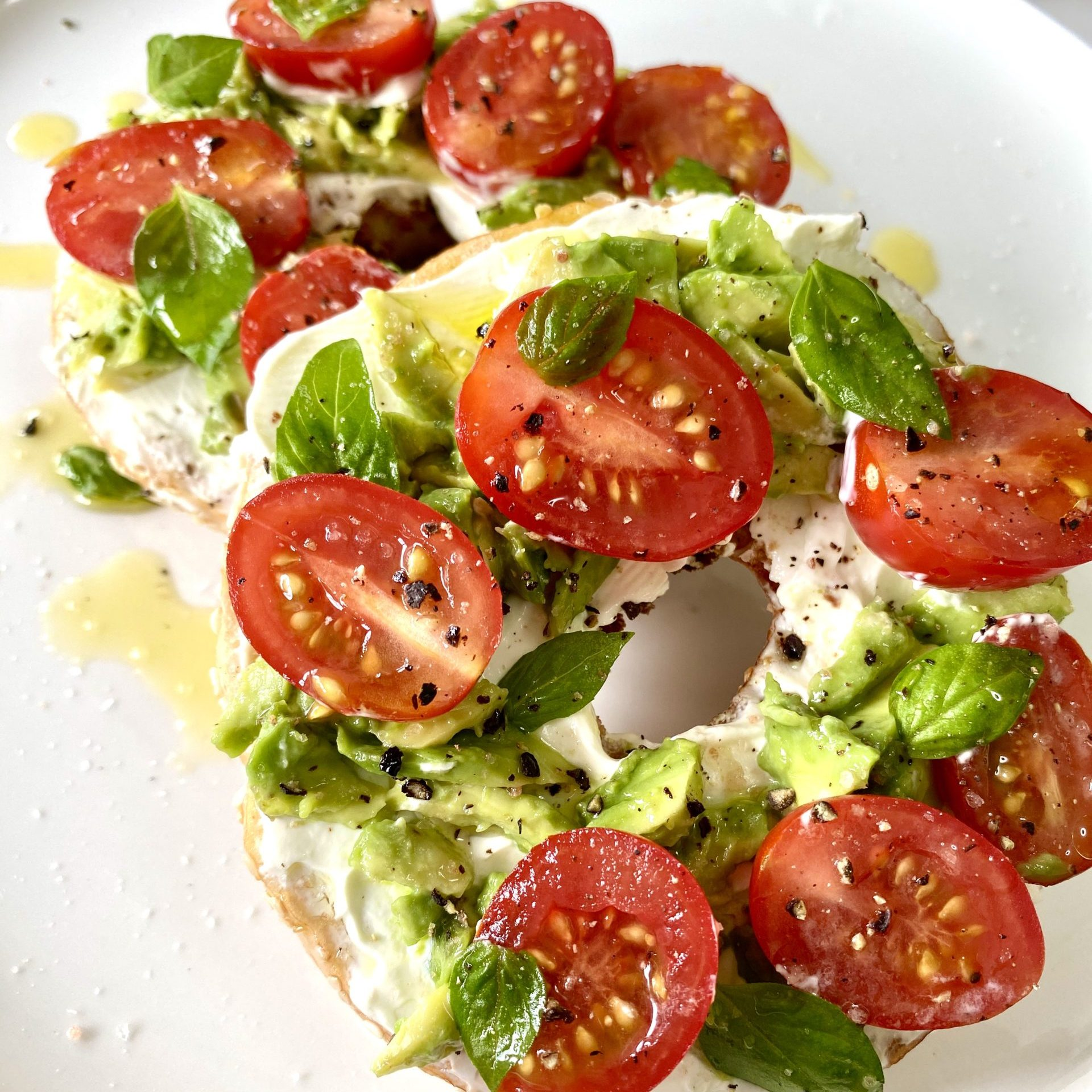 Avocado tomato and basil bagels with lemon and fennel infused olive oil drizzle