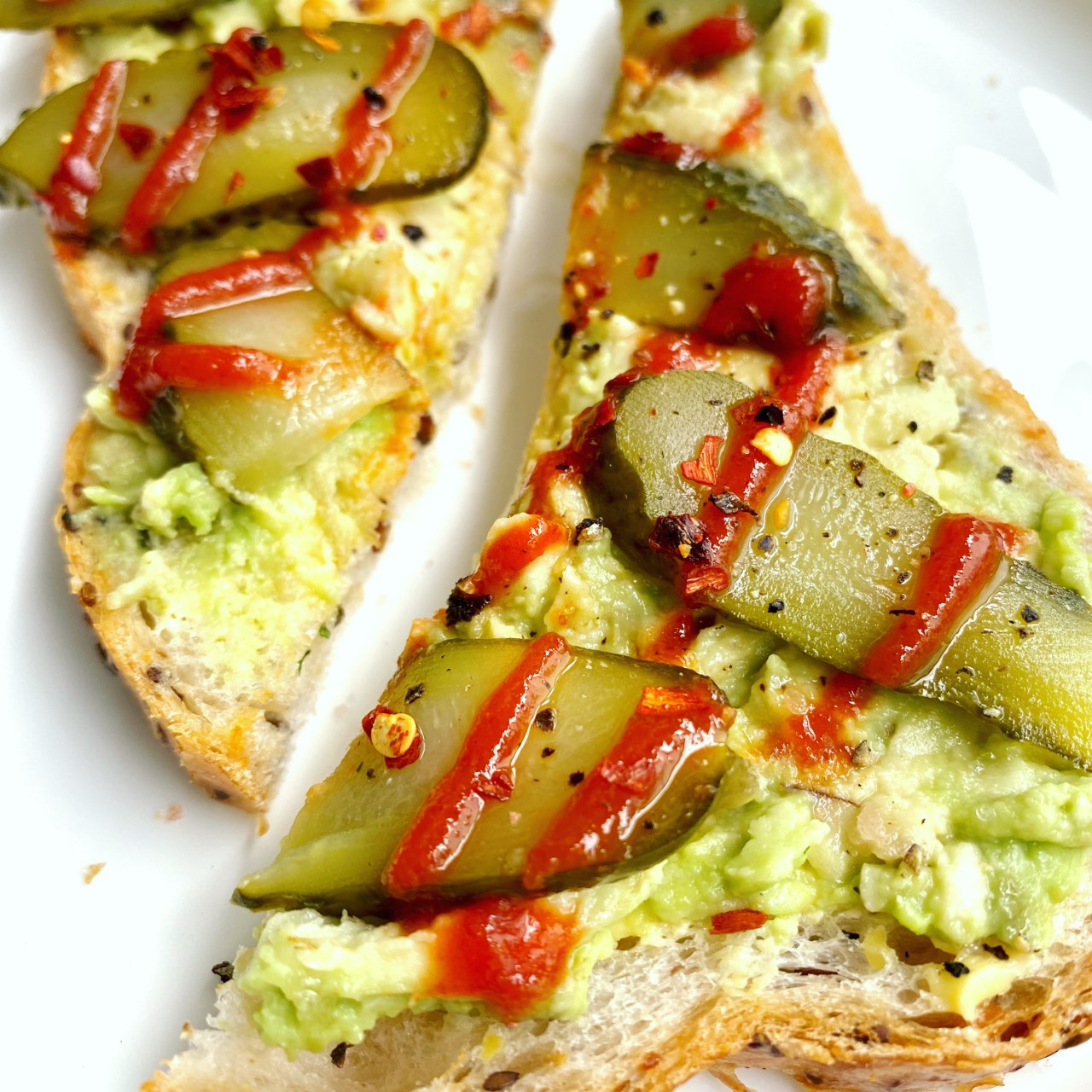 Avocado toast with pickles and sriracha hot sauce